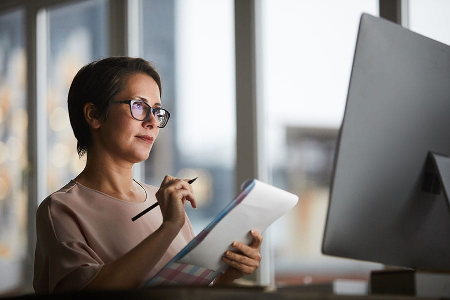 Woman assessing risk at desktop computer